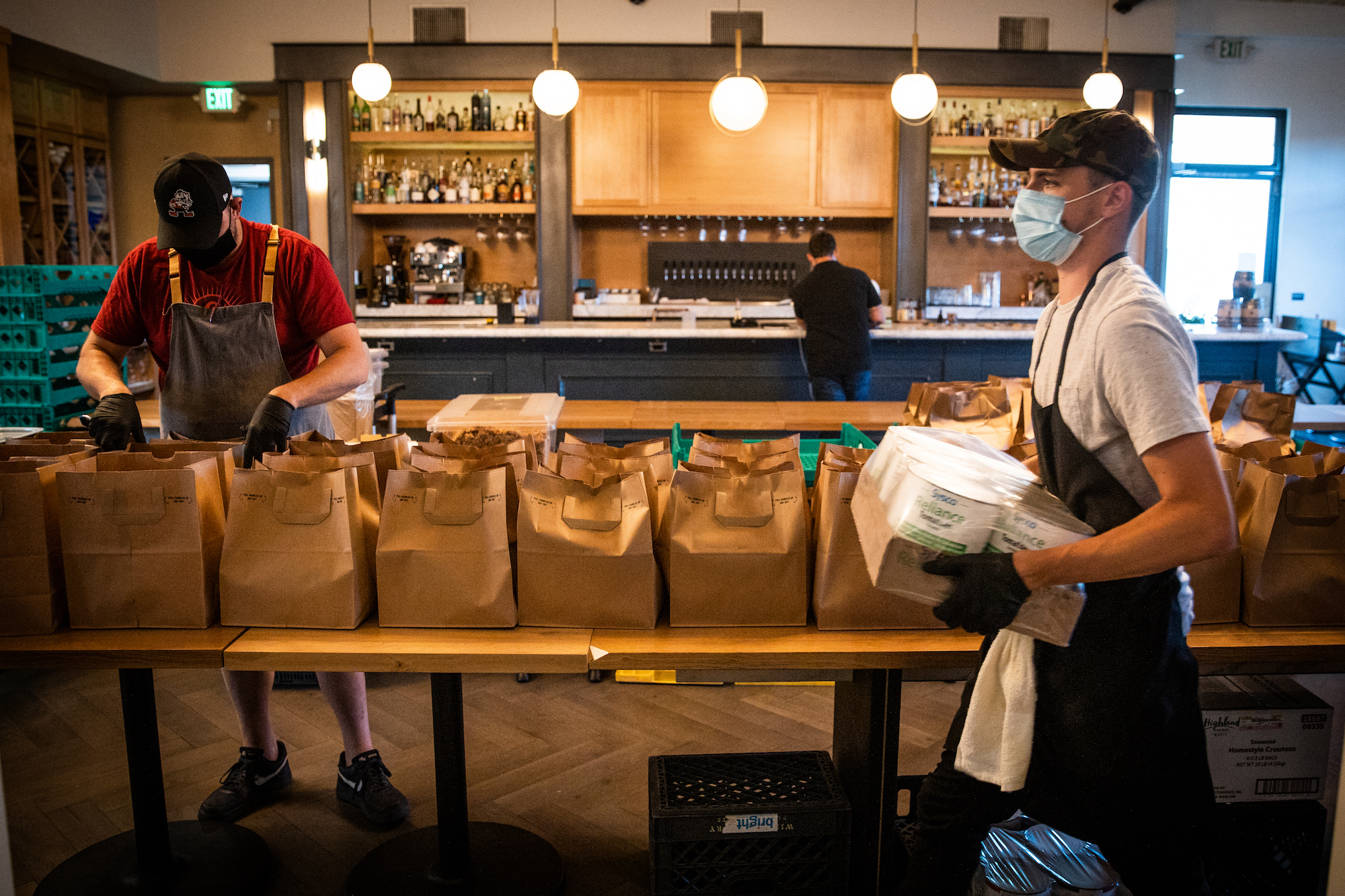 """Brad Cecchi, executive chef of Canon, left, and Bucky Bray pack up meals for the """"Family Meal"""" program at the restaurant in Sacramento, May 1, 2020. As part of the """"Family Meal"""" program, Canon is providing roughly 1400 meals per week for low income residents in the Sacramento area."""