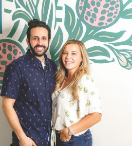 From left: Maydoon's husband-and-wife owners Idean and Jen Farid in front of a leaft mural