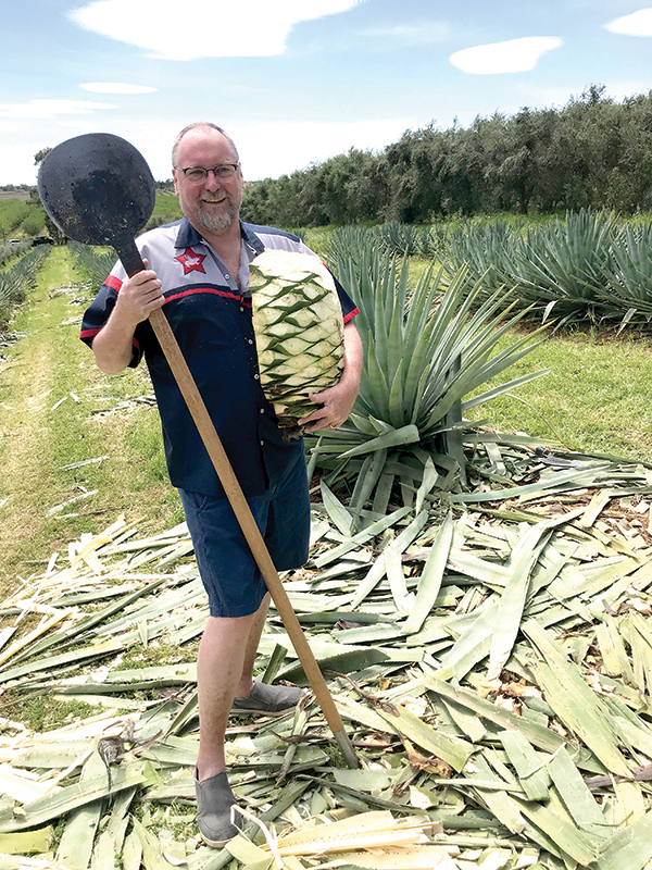 Chef Patrick Mulvaney at Reynolds' 2019 harvest holding a coa and a piña, the heart of an agave plant. (Photo courtesy of Craig Reynolds)