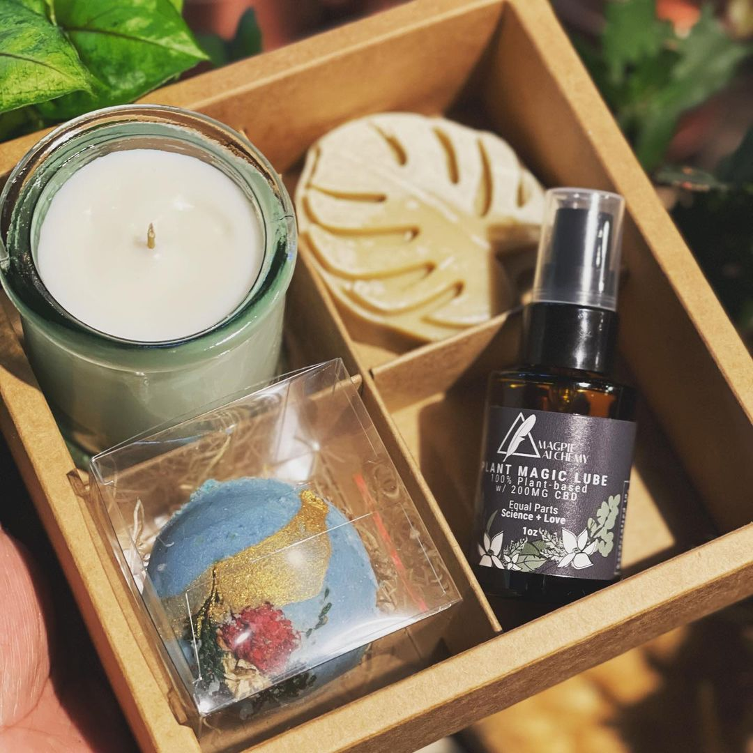 A box from Magpie Alchemy with a shower melt, candle, bath bomb and CBD lube.