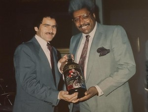 Mario Ortiz with Don King, holding a bottle of wine Ortiz painted.