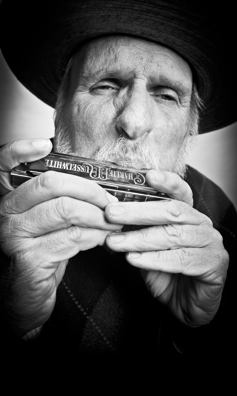 Mick Martin in black and white playing his harmonica