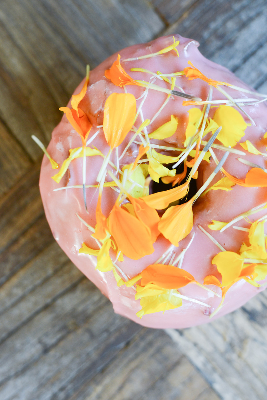 A pink doughnut topped with edible flowers