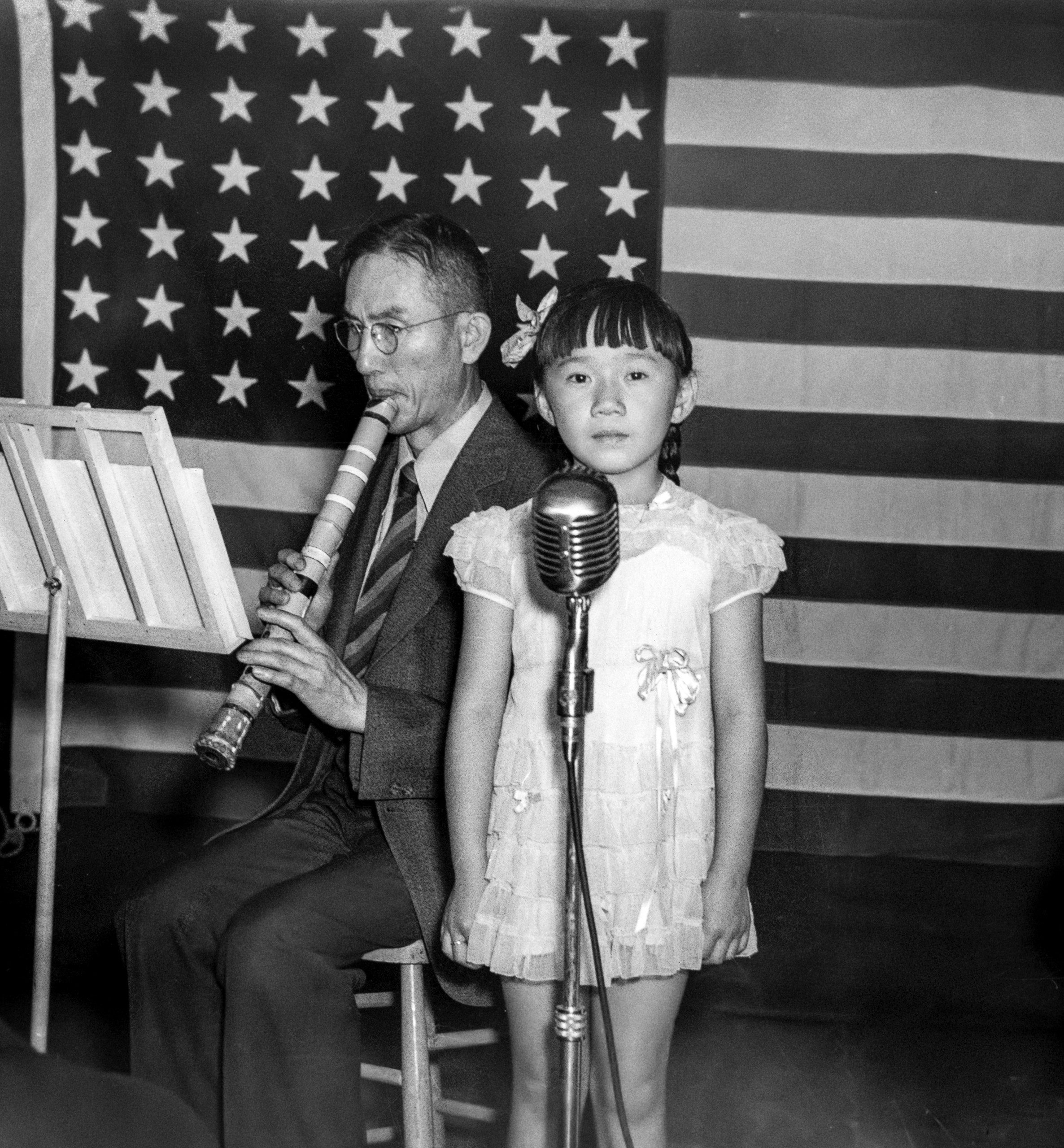 Photo of young Anna Kaku standing behind a microphone